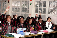 A Group Of Students In A Classroom Raise Their Hands To Answer A Question