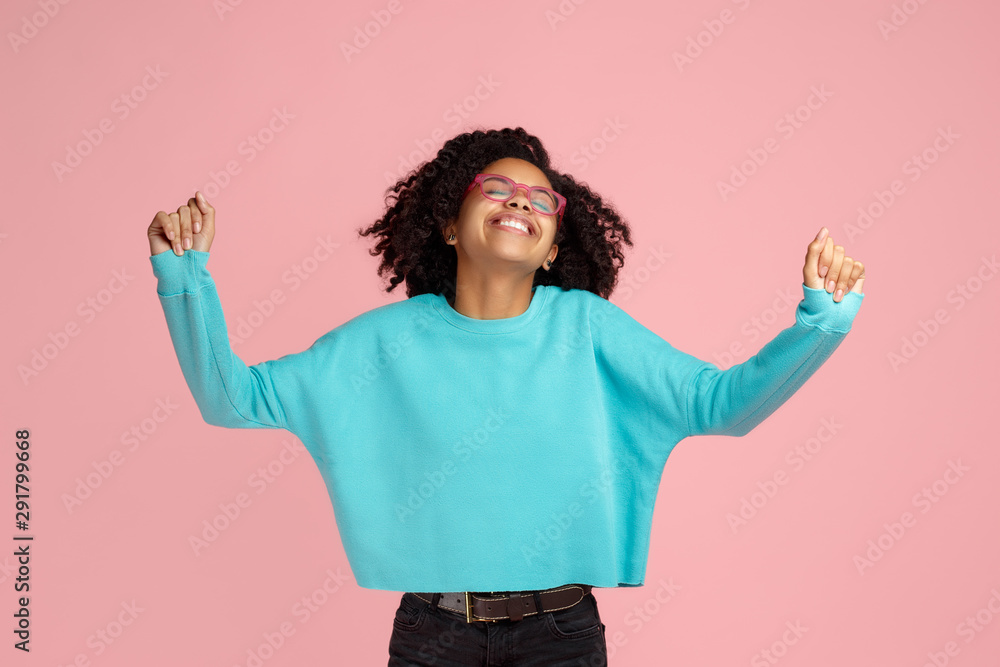 Fototapeta Photo of excited screaming african american young woman standing over pink background.