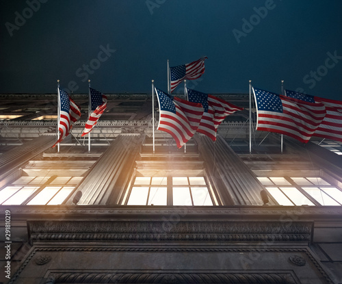 Vászonkép  american flags in front of building flying patriot night look epic historic insp