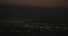 Aerial Helicopter Wide Shot, Airplane Landing At The Tail End Of Sunset Over A Small City, Lights Twinkling, Drone Footage