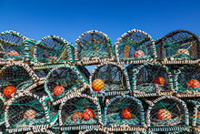 A Pile Of Lobster Pots Stacked Near The Coast Of Benbecula In The Western Isles, With A Blue Sky Overhead