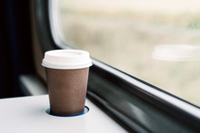 A Paper Coffee Cup With A White Plastic Lid. Coffee To Go On A Table In The Train Overlooking A Beautiful Rural Green Landscape. Travel, Lifestyle