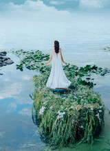 A Mysterious Woman In A Long White Dress Is Floating In A Boat To Meet The Blue Sky And Clouds. Decor With Grass, Branches And Flowers. Unusual Creative Wedding. Shooting From The Back Without A Face