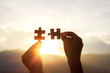 Silhouette hands holding piece of jigsaw puzzle sunset background. teamwork concept