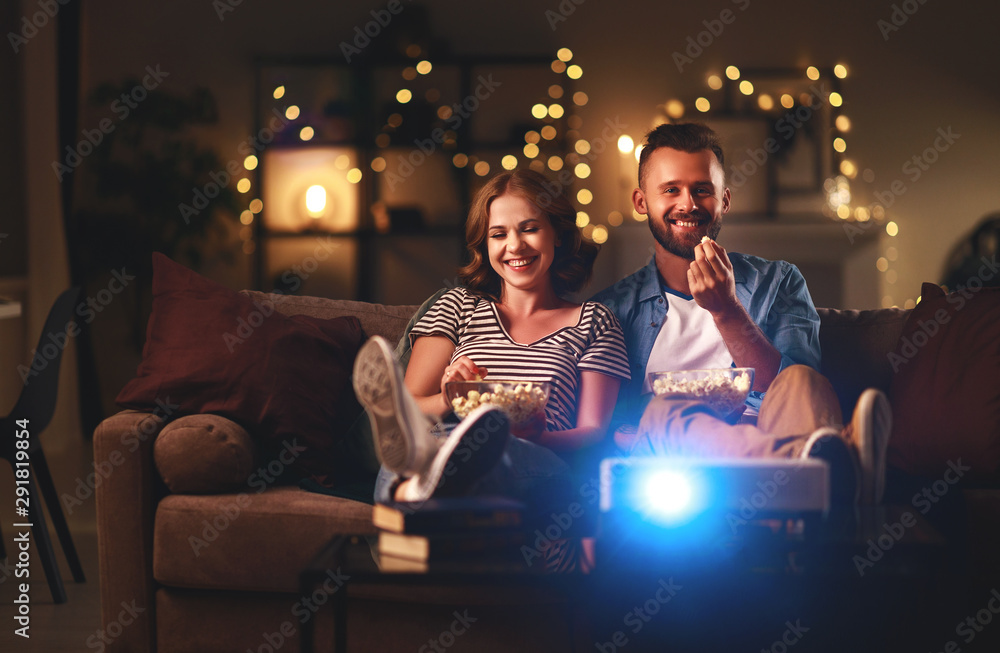 Fototapeta Family couple watching television at home on sofa