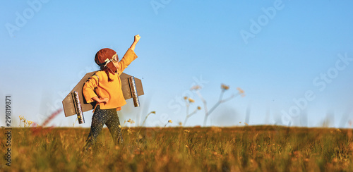 Fotografia Child pilot aviator with wings of airplane dreams of traveling in summer  at sun