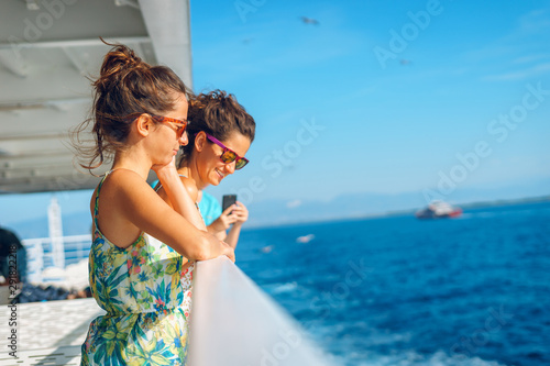 Fotomural Two young women girl friends sisters standing by the fence on deck of the ferry