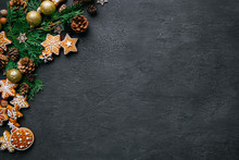 Christmas Background With Homemade Gingerbread Cookies, Evergreen Branches And Decorations On Black Table. Festive Food, New Year Celebration Traditions