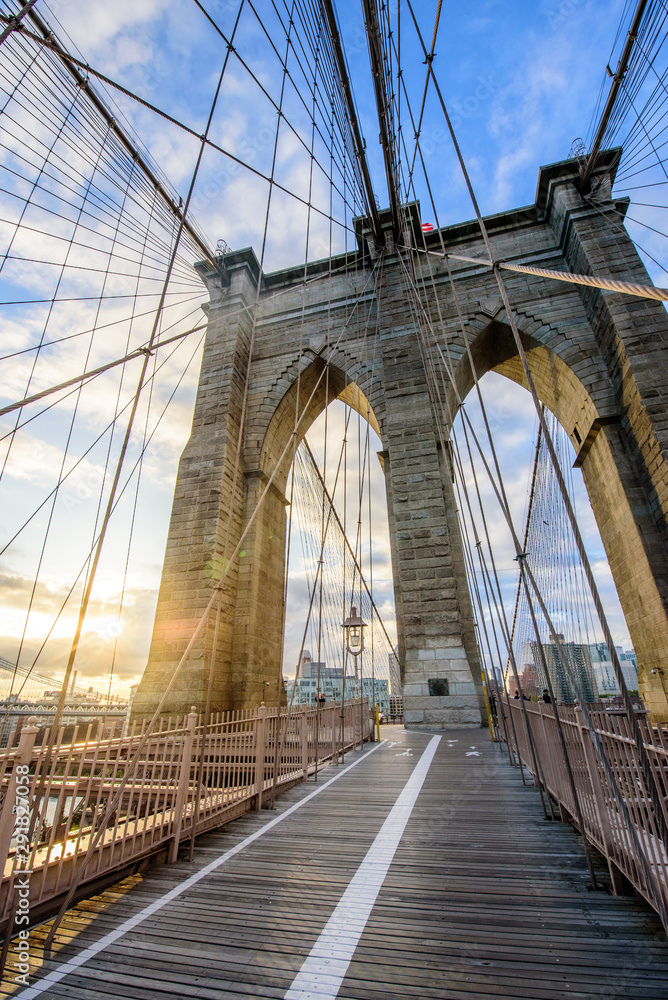 Fototapety, obrazy: Sun shines through the Brooklyn Bridge with views of Manhattan during Sunrise