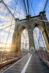 Sun shines through the Brooklyn Bridge with views of Manhattan during Sunrise