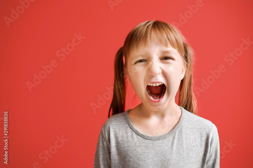 Fotografiet Portrait of angry little girl on color background
