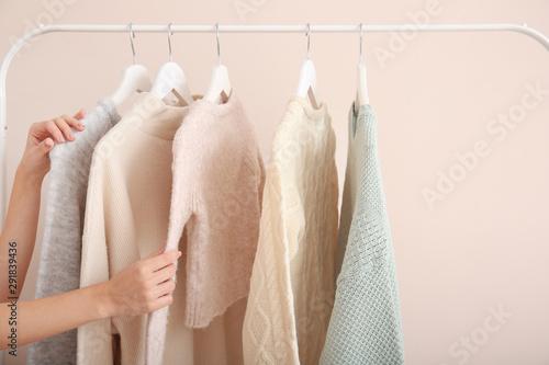 Obraz na plátně  Woman choosing clothes hanging on rack