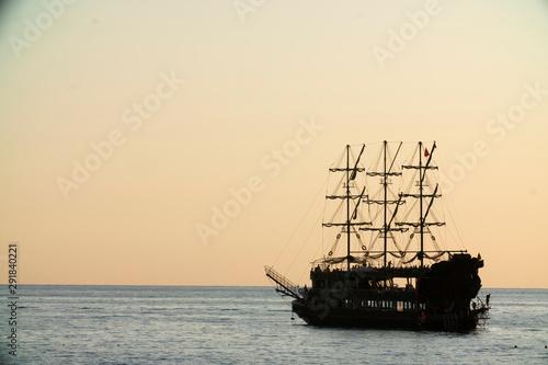 Türaufkleber Schiff old pirate ship sailing at sea sunset