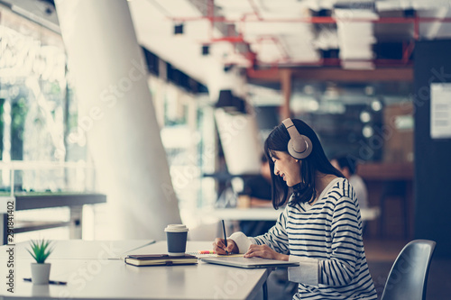 Young Asian girl listening the music with headphones and reading books while sitting at the table in the modern working space. - 291841402