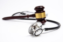 A Wooden Judge Gavel And Stethoscope Isolated On White Background. Medical Dispute Concept.