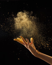 Beautiful Photo Of Female Hand Throwing Gold Dust On A Black Background With Copy Space. Layout For Your Ideas.