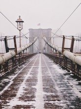 A Symmetrical View Of The Brooklyn Bridge During A Snow Storm In December.