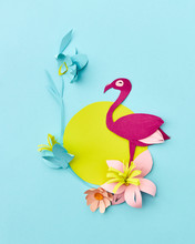 Colored Pink Flamingo On A Handcraft Decorative Frame With Exotic Flowers On A Pastel Blue Background. Flat Lay.