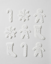 Pattern From Volumetric Paper Figures In The Form Of Snowmen, Snowflakes, Socks And Candy On A Gray Background. Christmas Composition As A Layout. Flat Lay