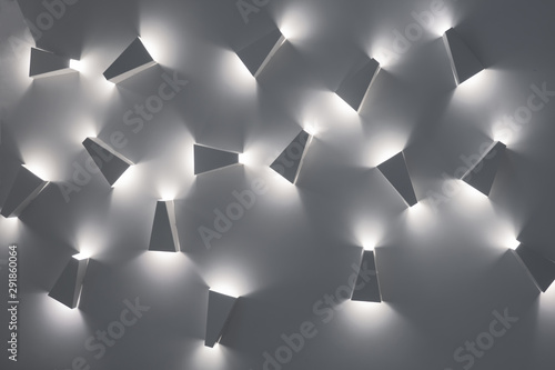 Obraz Light fixtures, unusual ceiling lamps. Design pattern. Cold lights. White colors of pattern. Modern design lighting. Contemporary interior lightning design. Modern indoor lighting concept - fototapety do salonu