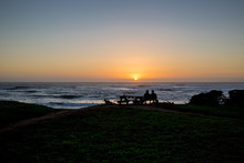 Couple Watching The Sunset With Their Dog Nearby