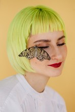 Stylish Young Woman With Short Yellow Hair And Butterfly Sitting On Her Face