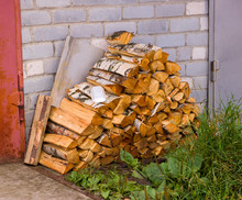 Firewood Stacked In A Woodpile Near The Garage