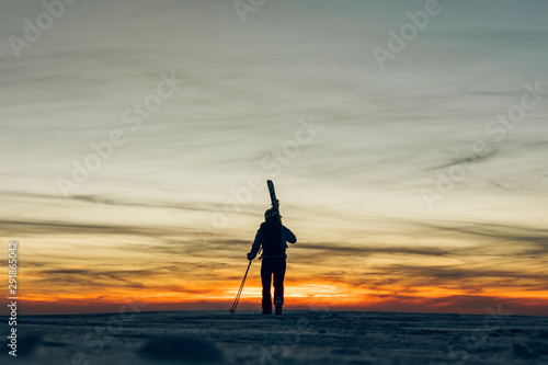 Silhouette of Skier carrying her skis at sunset