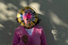 Teenage Girl Blowing Pinwheel Toy