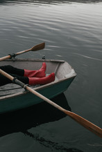 Woman Rest Red Rubber Boots On Seat Of Wooden Rowboat