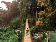 Young Man Walking On Footbridge Above River Between Tropical Forest