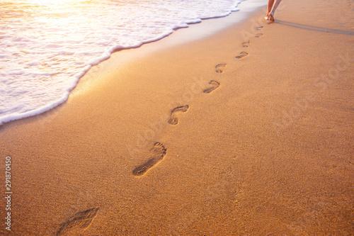 Obraz beach, wave and footprints at sunset time - fototapety do salonu