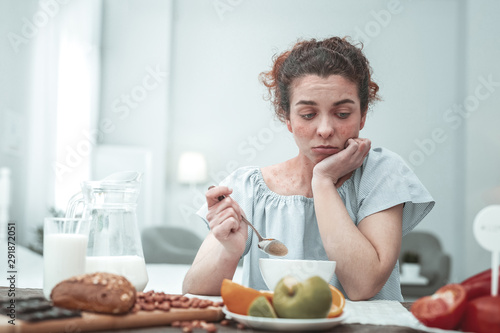 Curly woman not knowing what to eat while having allergy Wallpaper Mural