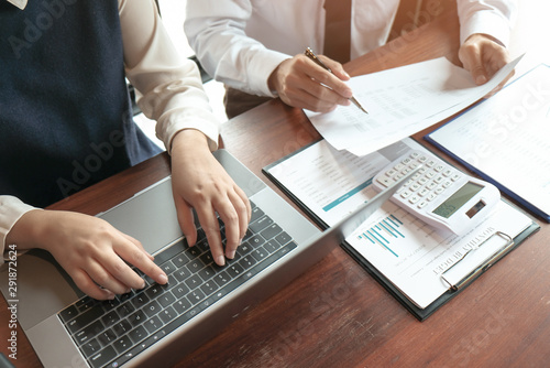 Businessman analyzing investment charts and pressing calculator buttons over documents Canvas Print