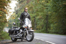 Bearded Tall Motorcyclist In Dark Sunglasses, Black Leather Jacket Standing At Shiny Modern Powerful Cruiser Motorbike On Blurred Background Of Hilly Asphalt Road And Green Trees.