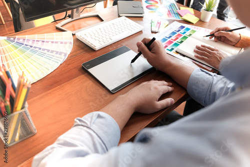 Graphic designer working on digital tablet. artist drawing on graphic tablet and Color swatch samples.