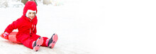Pretty Smiling Little Girl In Her Ski Suit Sliding Down A Small Snow Covered Hill With Her Sledge