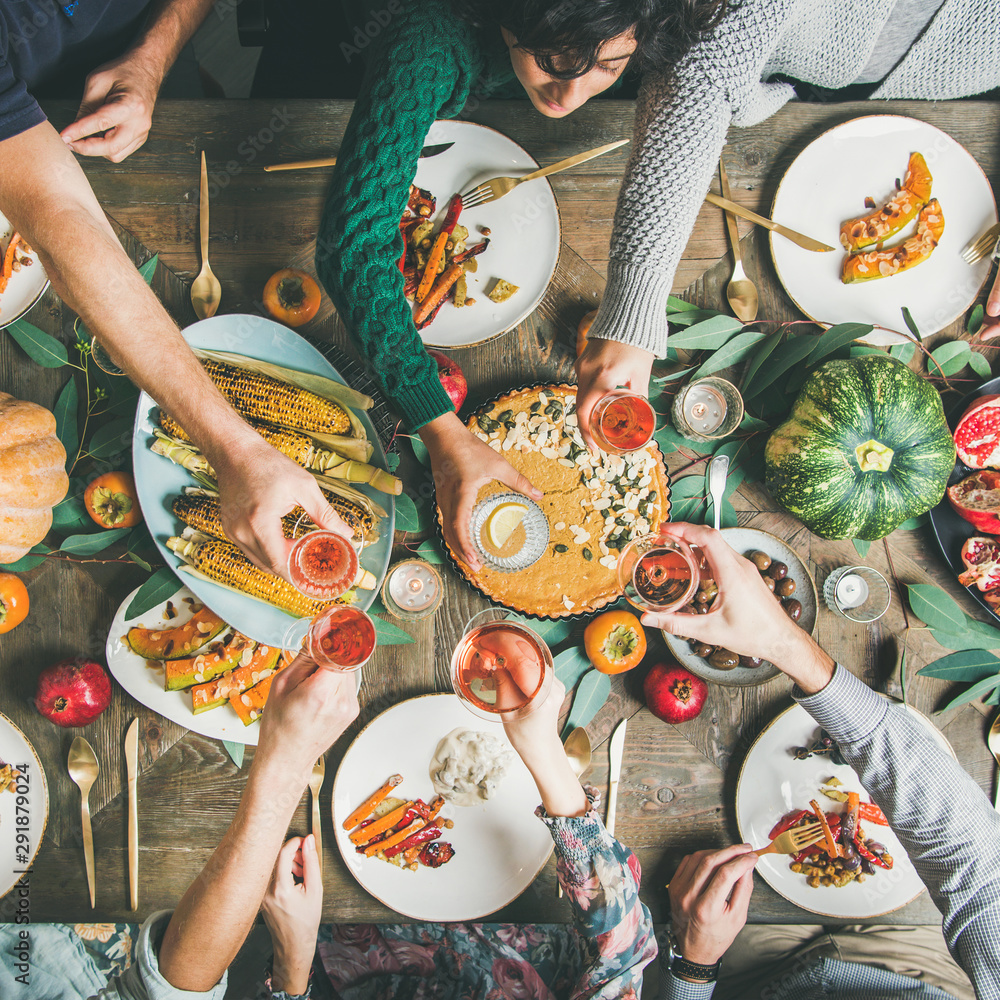 Fototapeta Vegan, vegetarian Thanksgiving, Friendsgiving holiday celebration. Flat-lay of friends clinking glasses at Thanksgiving Day table with pumpkin pie, vegetables, fruit and wine, top view, square crop