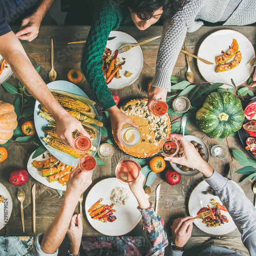 Vegan, vegetarian Thanksgiving, Friendsgiving holiday celebration. Flat-lay of friends clinking glasses at Thanksgiving Day table with pumpkin pie, vegetables, fruit and wine, top view, square crop - 291879024
