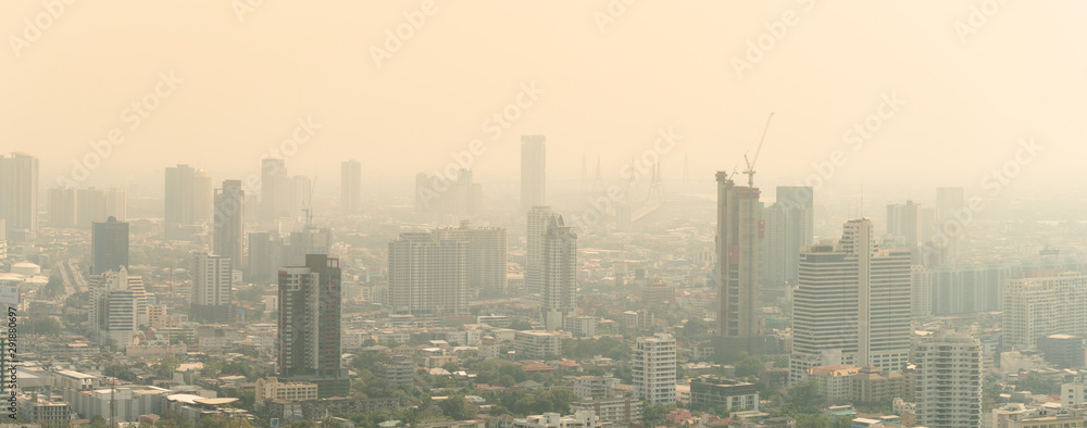 Fototapeta PM2.5 Unhealthy air pollution dust smoke in the urban city. Low visibility city view with dangerous haze and fog. Smog Bangkok city.