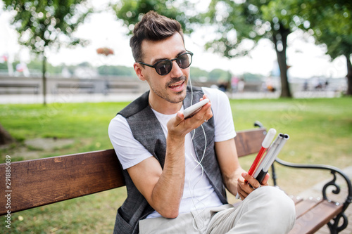 Young blind man with smartphone sitting on bench in park in city, calling Canvas Print