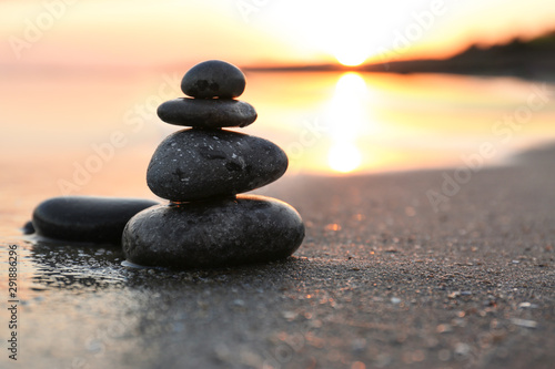 Staande foto Stenen in het Zand Dark stones on sand near sea at sunset, space for text. Zen concept