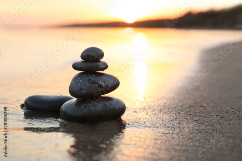 Zen pierres a sable Dark stones on sand near sea at sunset, space for text. Zen concept