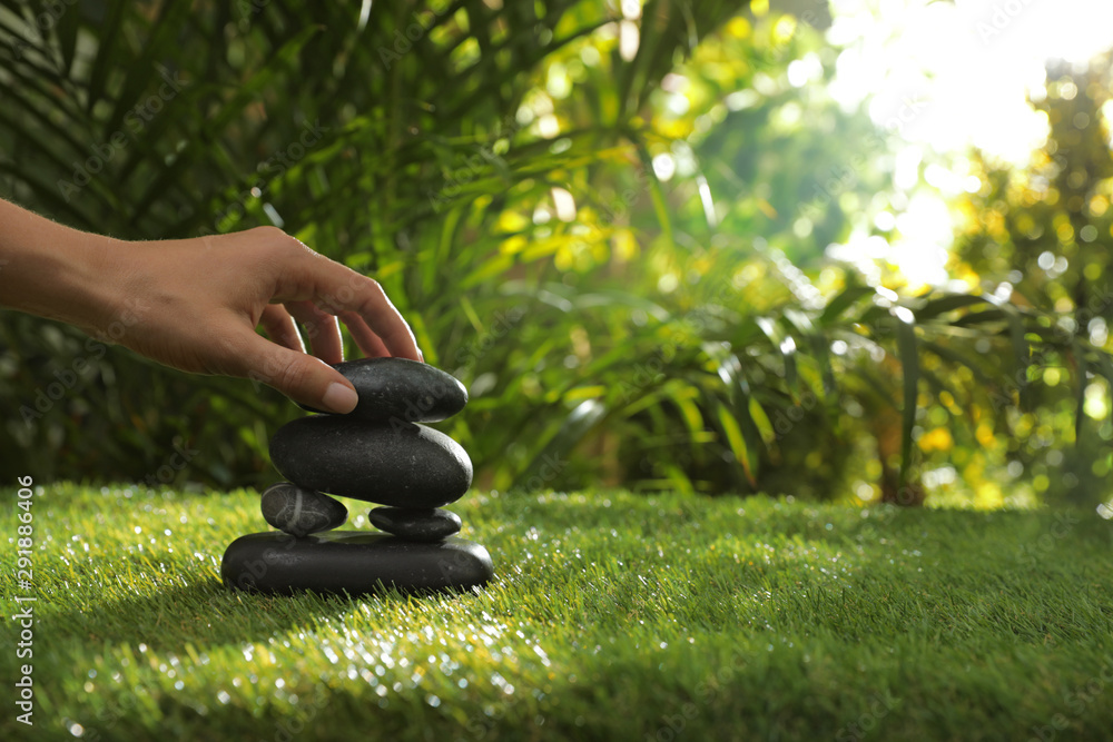 Fototapeta Woman stacking stones on green grass in garden, closeup. Space for text