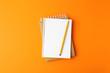 Leinwandbild Motiv Notebooks with pencil on orange background, top view