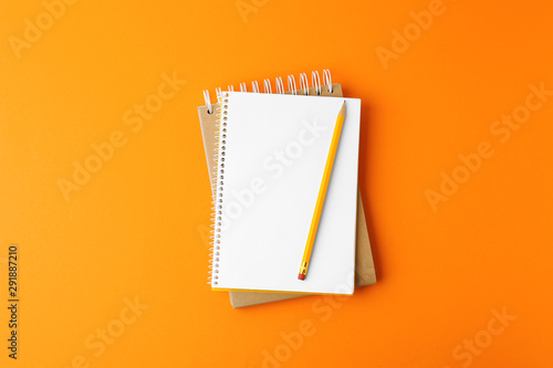Photo  Notebooks with pencil on orange background, top view