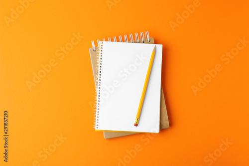 Carta da parati  Notebooks with pencil on orange background, top view