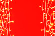 Leinwandbild Motiv Christmas lights on red background, top view. Space for text