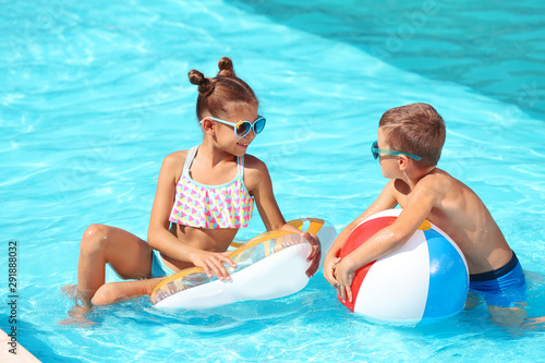 Photo Cute little children with inflatable toys in swimming pool
