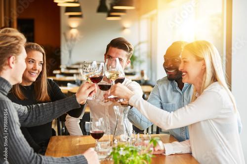 Obraz na plátně  Freunde stoßen mit Wein an bei Geburtstag